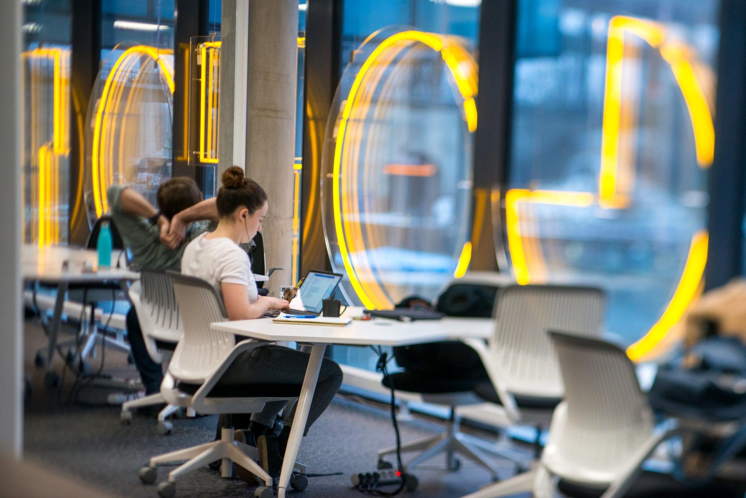 En kvinna och man sitter och arbetar vid en laptop på Goto 10 coworkingspace