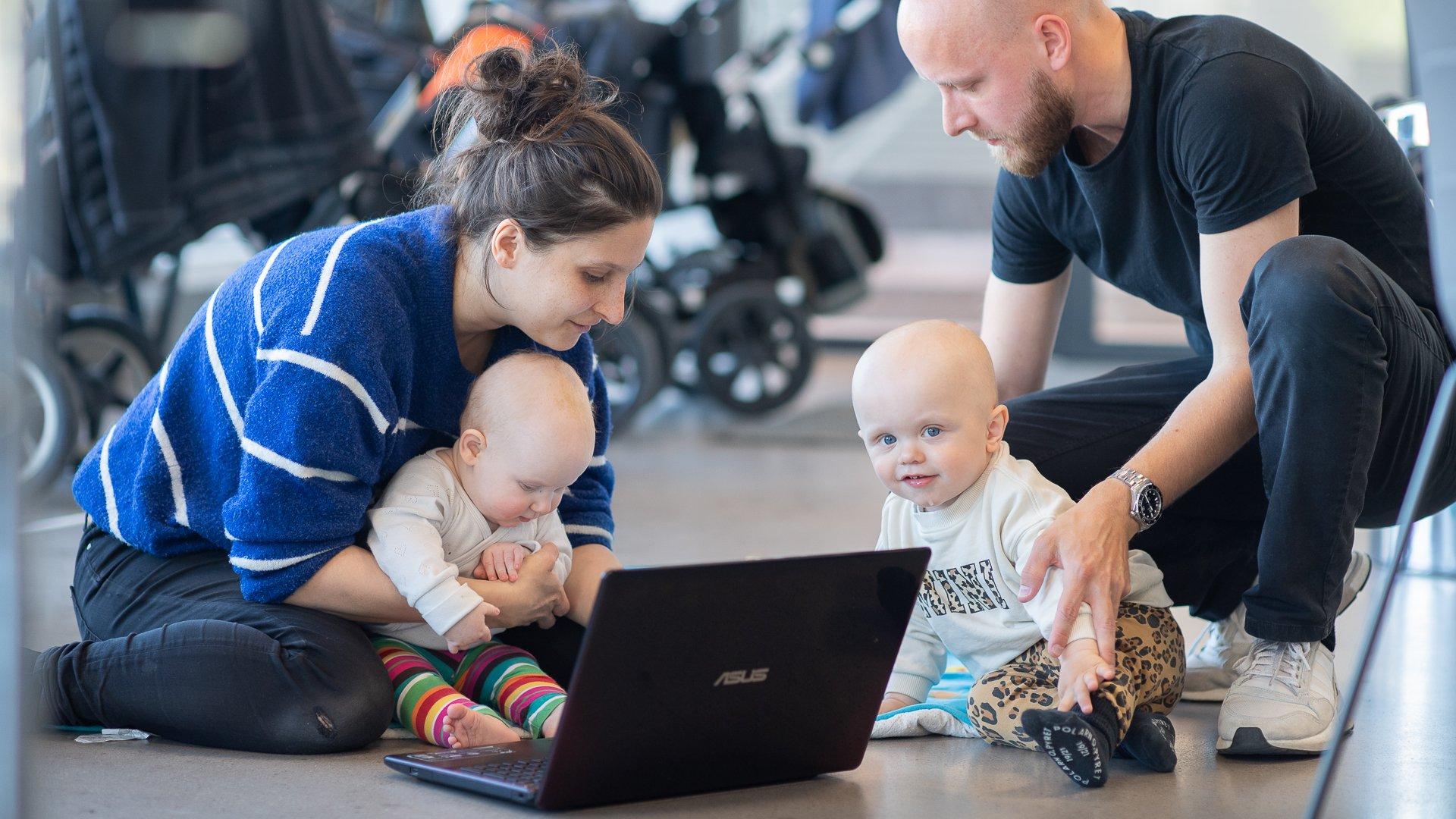En mamma och en pappa sitter på golvet med varsitt barn framför sig på Goto 10 Stockholm.