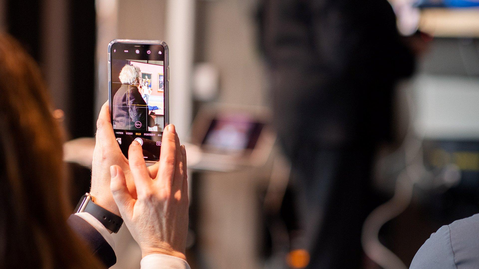 Kvinna som tar foto på en föreläsare på Goto 10.