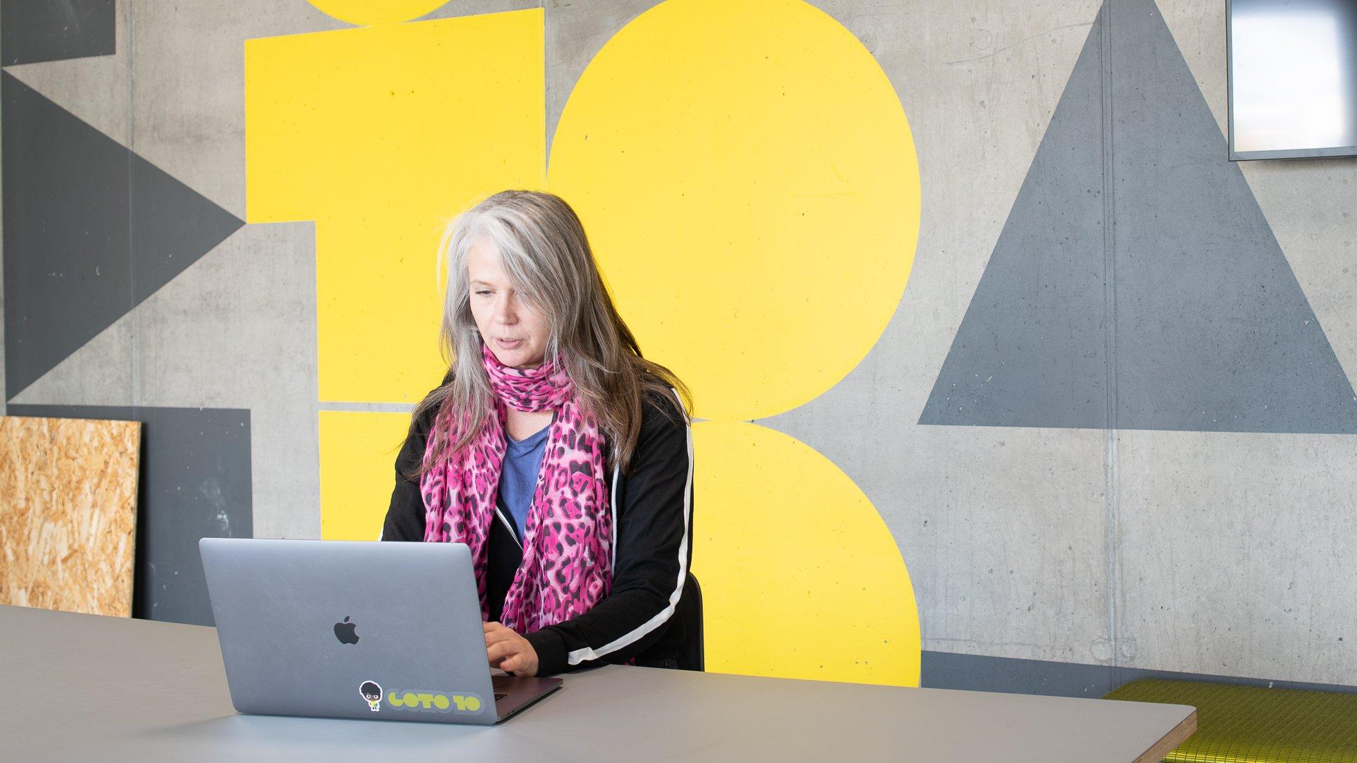 Kvinna sitter vid bord och skriver på sin laptop och sitter framför Goto 10-målning på väggen