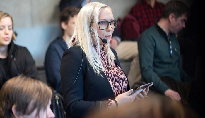 Moderator med headset-mikrofon håller i iPad och talar vid event på Goto10.