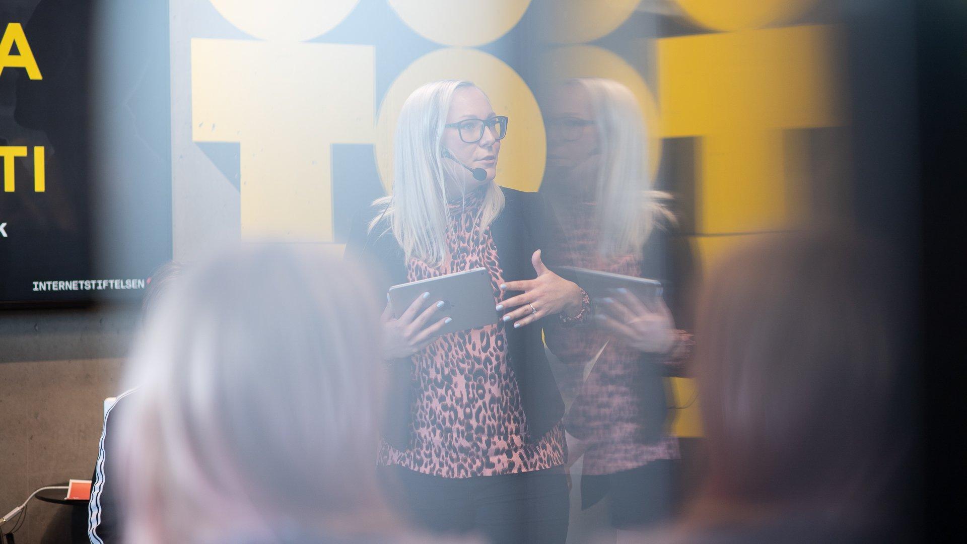Moderator med headset-mikrofon och iPad talar framför publik under panelsamtal på Goto10.