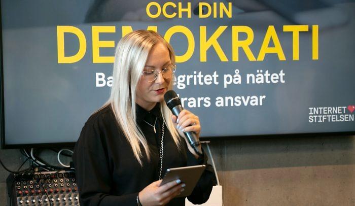 Kvinna håller i mick och presenterar ett seminarium