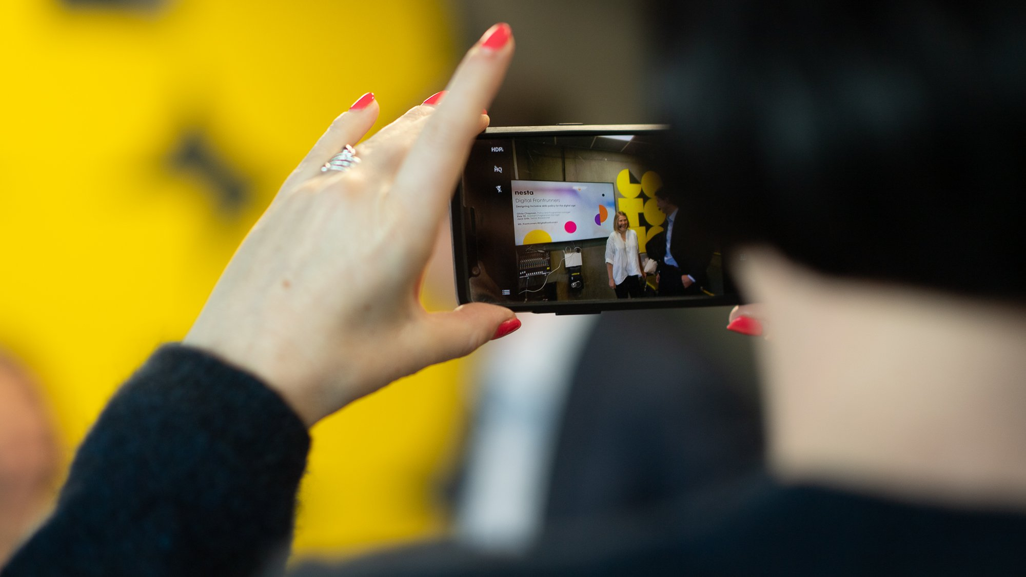 Kvinna sedd bakifrån fotograferar event på Goto10 med mobilkamera.