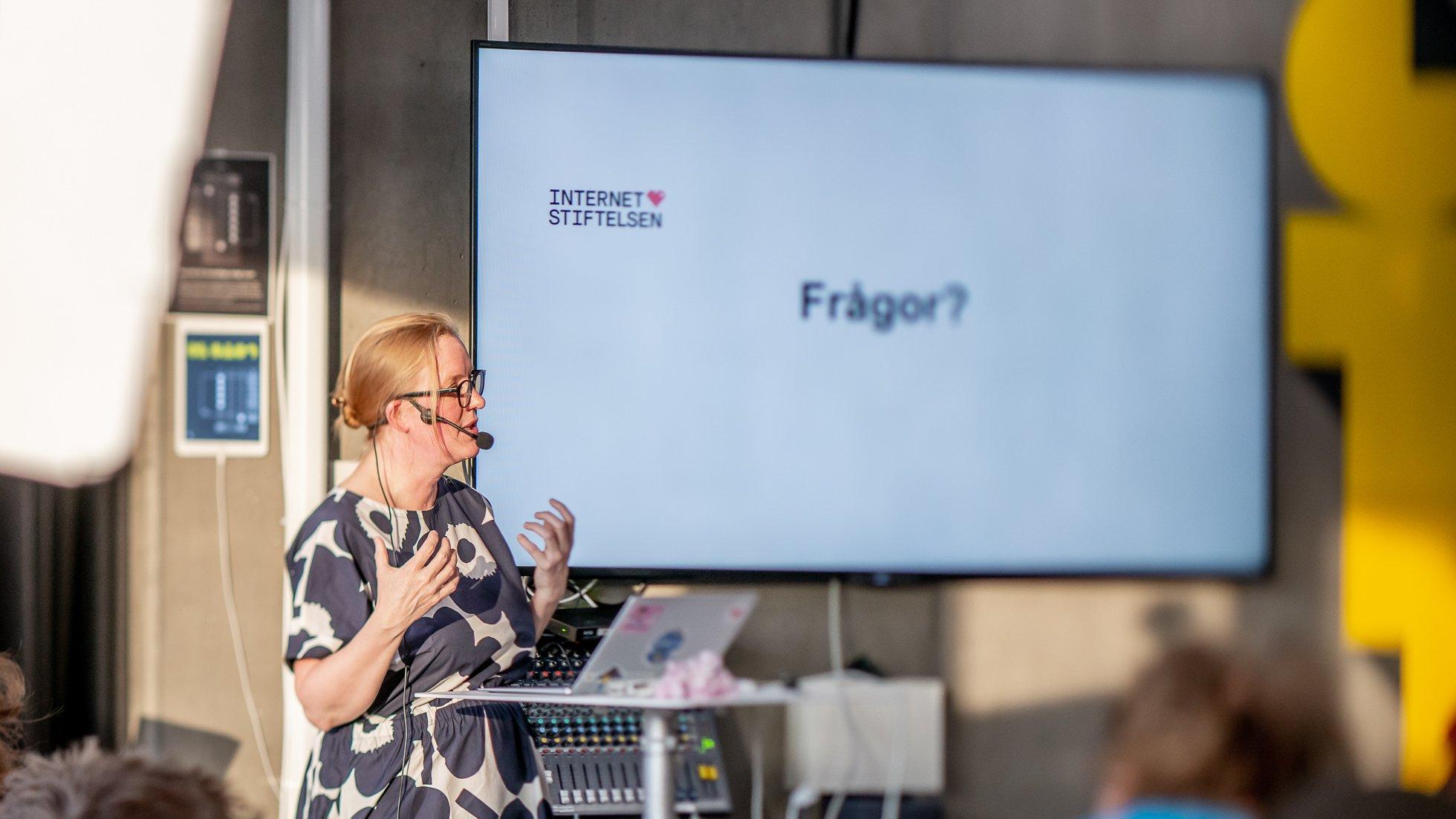 En föreläsare står vid ett ståbord med en presentationsskärm bakom sig på väggen med ordet Frågor
