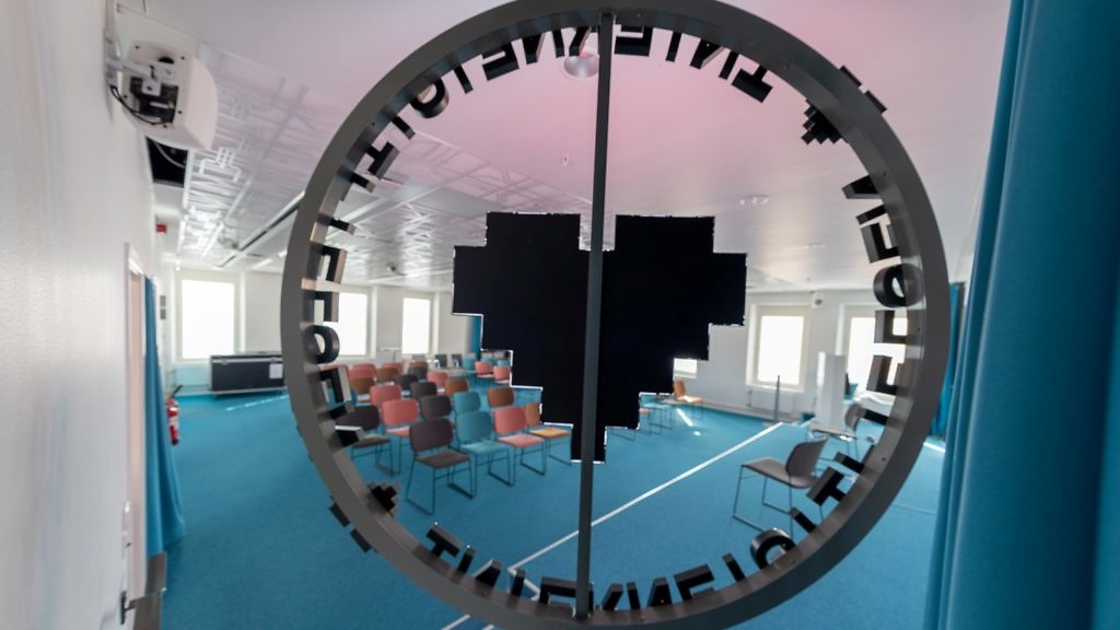 Konferensrum syns genom en logga
