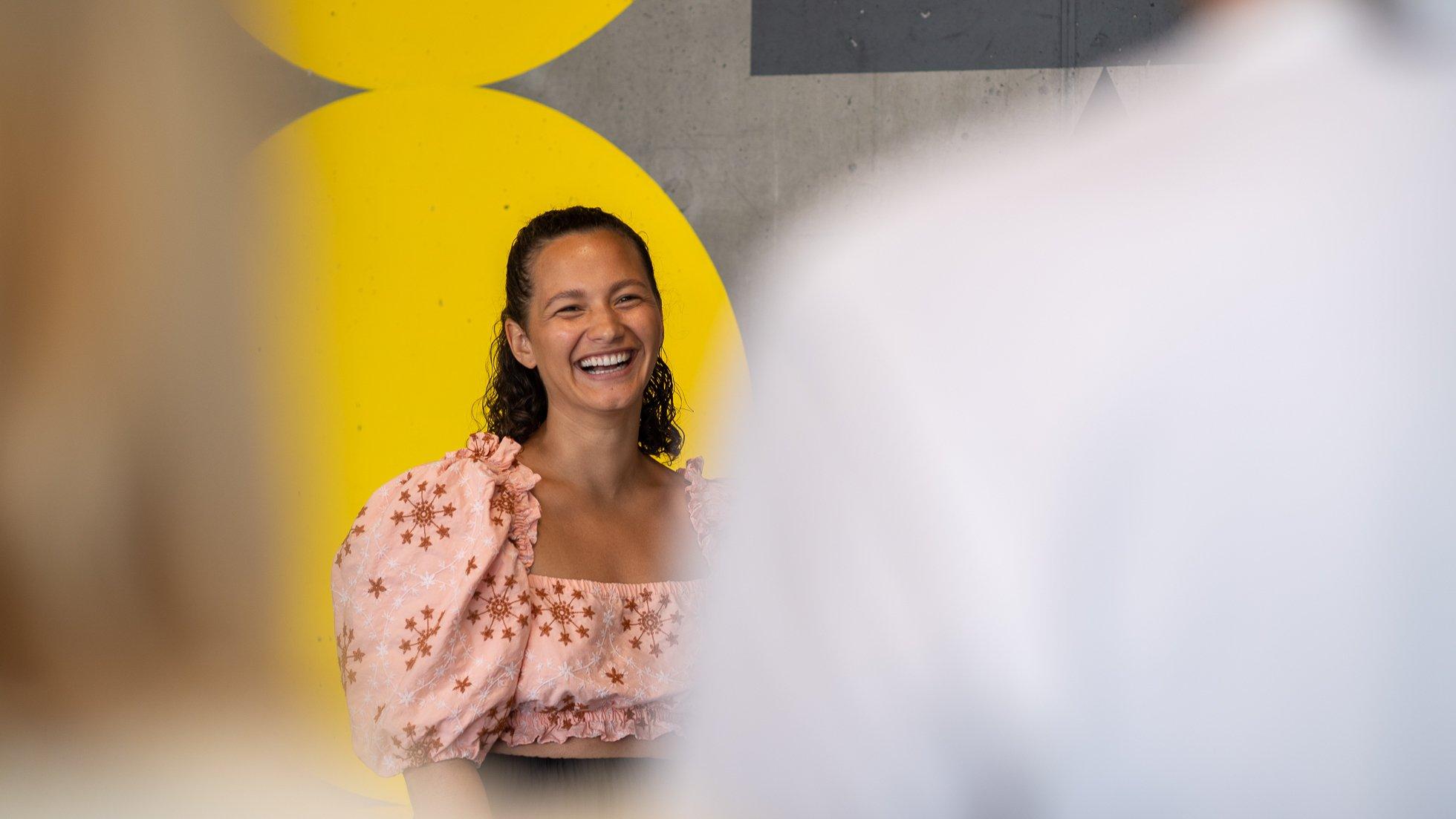 Skrattande kvinna står framför målad tegelvägg i gult och tittar in i kamera m