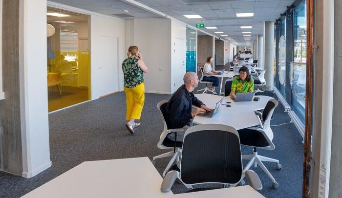 Personer som sitter och jobbar i kontorsmiljö.
