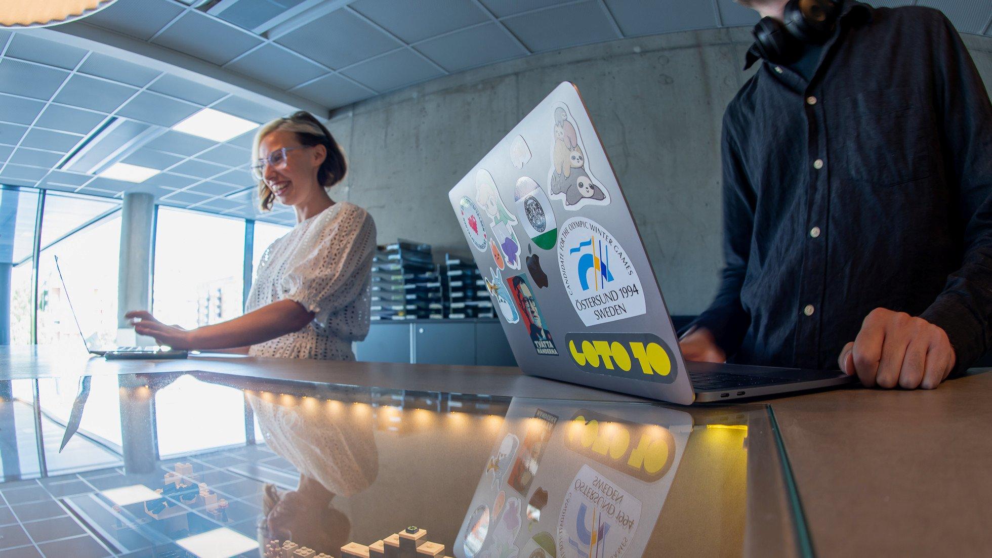 En man och en kvinna står bredvid varandra vid ett bord med sina laptops framför sig