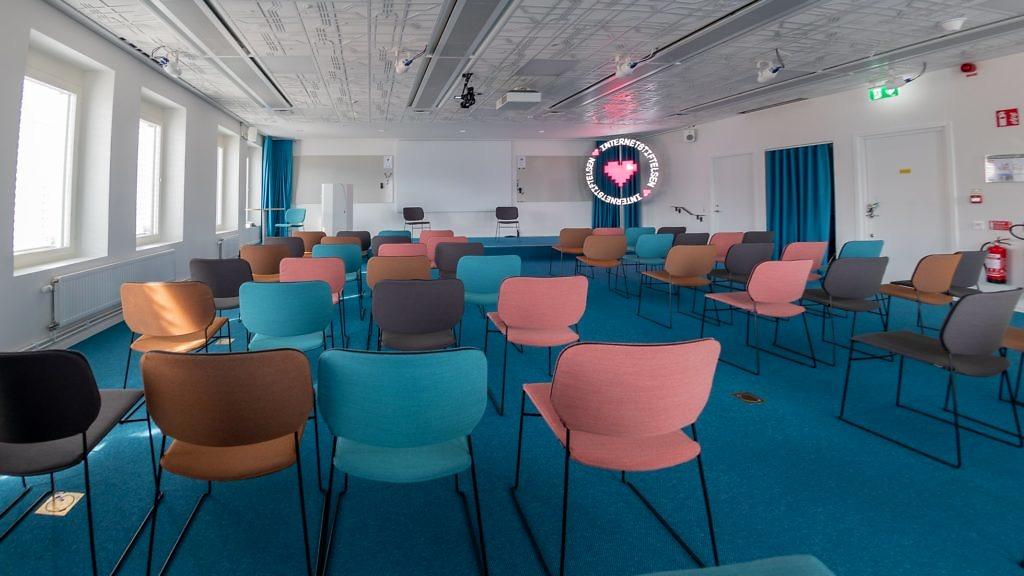 Baksidan av färgglada stolar längst bak i ett konferensrum.