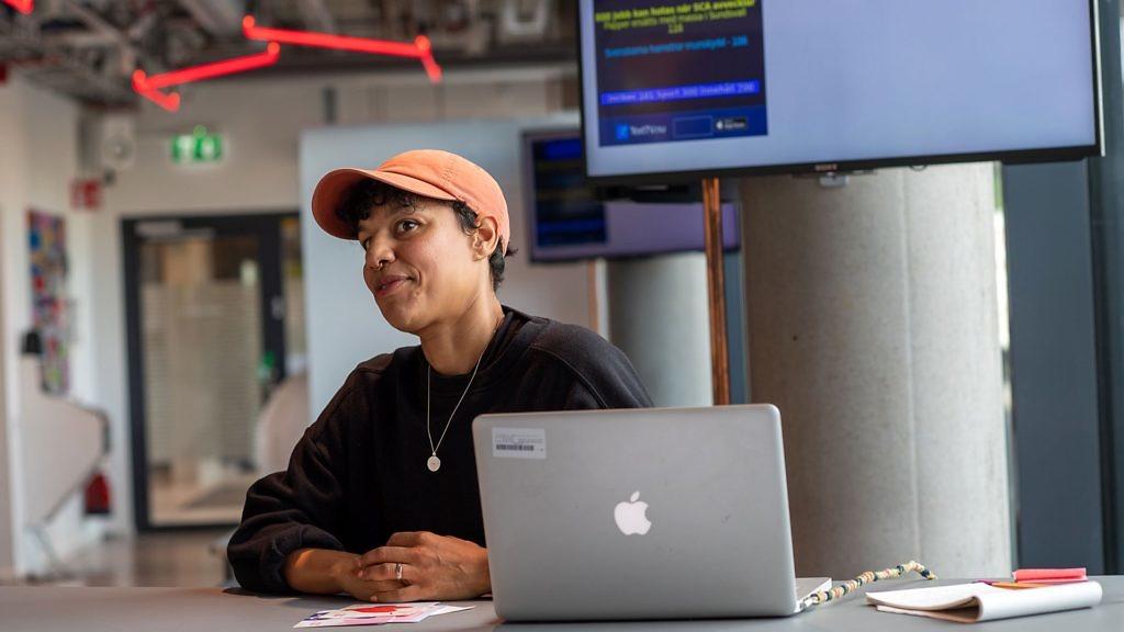 En leende kvinna med keps sitter och arbetar på en av de öppna arbetsplatserna på start- och mötesplatsen Goto 10 Stockholm.
