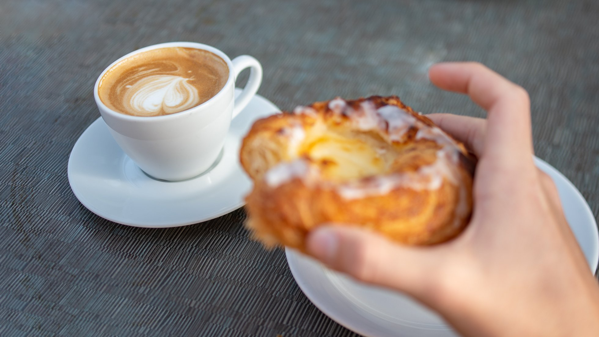 en kaffekopp med ett fat och en hand som håller i ett Wienerbröd