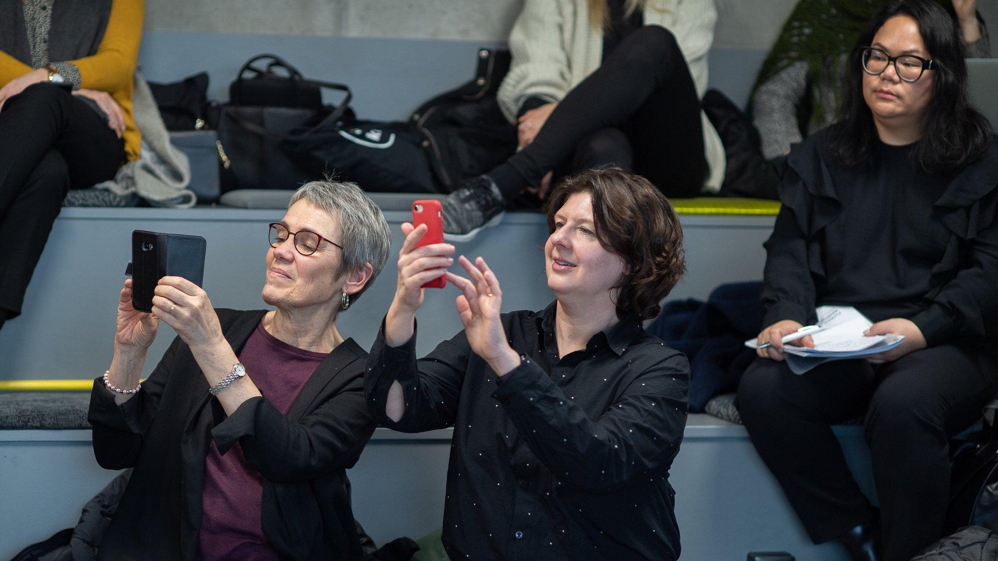 Publik vid event på Goto10. Två kvinnor i publiken fotograferar scenen med varsin mobiltelefon.