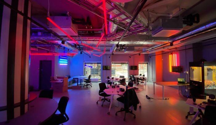 Arbetsyta med skrivbord, stolar och neonlampor på Goto 10 Malmö