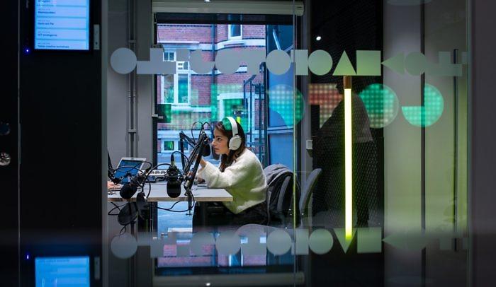 En kvinna sitter och poddar i poddstudion på Goto 10 Malmö