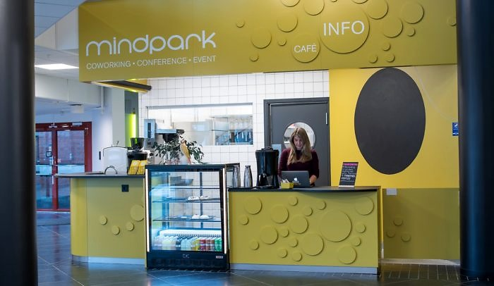 En kvinna står framför dator i disken på The Mindpark Café på Goto 10 Malmö